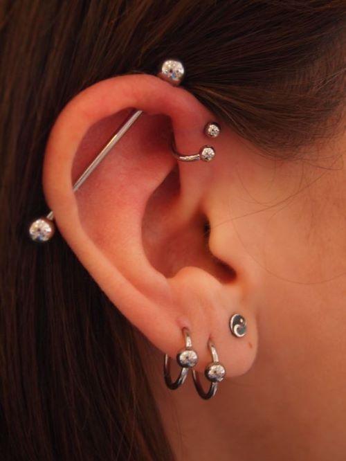 Piercing transversal ou industrial + anti helix complementado por três furos no lóbulo./ Reprodução: Pinterest