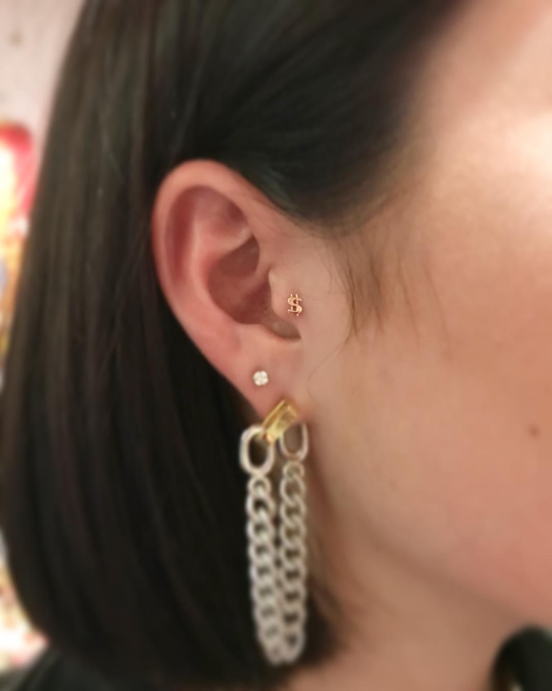 Piercings na orelha cifrão