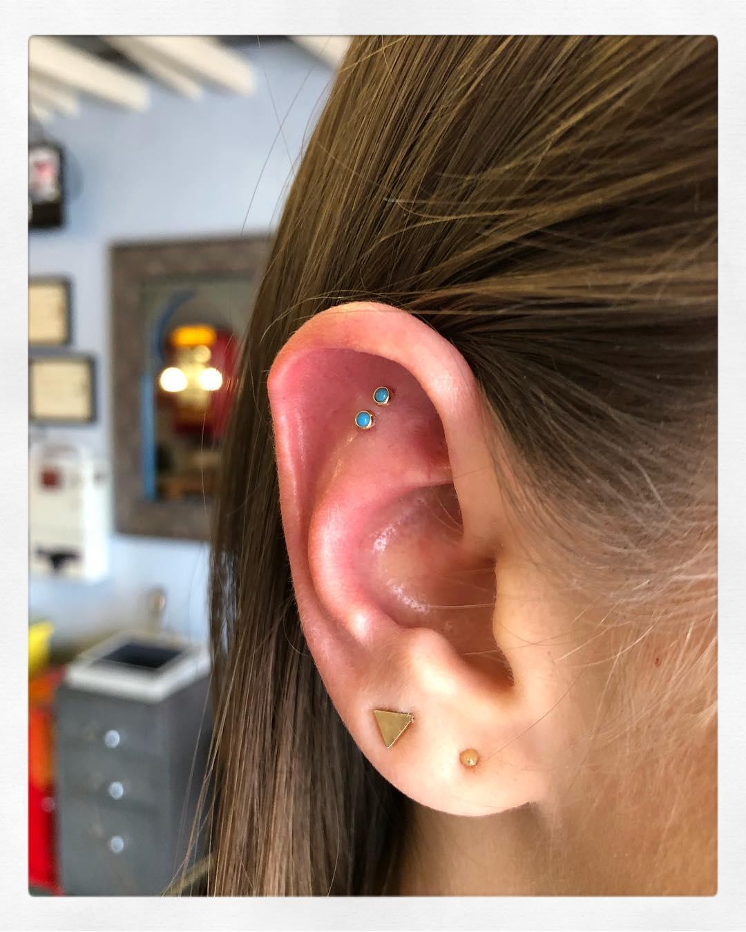 Piercings na orelha coloridos