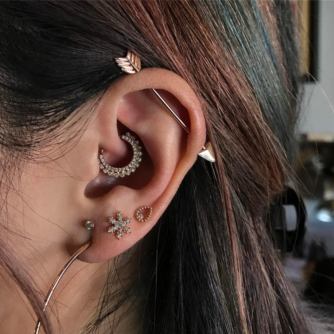 Piercings na orelha dourados
