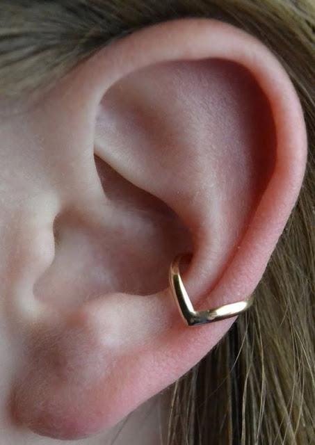 Piercings delicados na orelha ouro