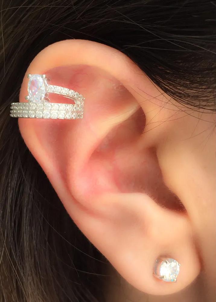 Piercings delicados na orelha oval