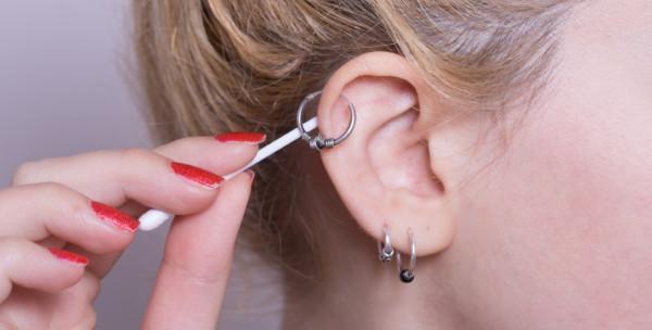 mulher mostrando como cuidar do piercing na orelha