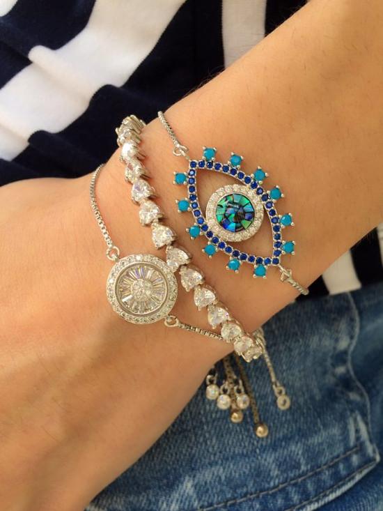 Braço de uma mulher usando várias pulseiras.