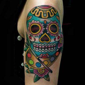 Braço tatuado com caveira mexicana colorida